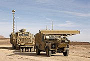 A Mastiff fitted with Choker Mine Rollers following on behind the Panama remote control Land Rover. The vehicles are in a flat desert in Jordan with a bright blue sky. At the front of the Land Rover, about six feet off the ground, is a horizontal beam which can be lowered in front of the vehicle to scan the ground with radar. The beam is approximately three metres wide.