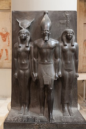 Bat (goddess) - Both Hathor (left) and Bat flank Menkaure in this Fourth Dynasty triad statue. The goddesses provide the authority for him to be king and are identified by their crowns. The emblem on Bat's crown represents the sistrum, though the crown also includes her zoomorphic face and the feather of Ma'at. - Cairo Museum
