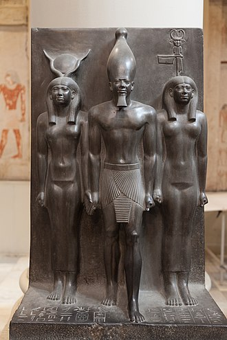 Bat (goddess) - Both Hathor (left) and Bat (right) flank Menkaure in this Fourth Dynasty triad statue. The goddesses provide the authority for him to be king and are identified by their crowns. The emblem on Bat's crown represents the sistrum, though the crown also includes her zoomorphic face and the feather of Ma'at. - Cairo Museum