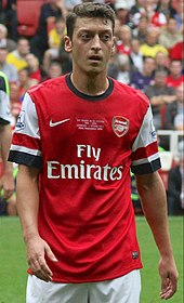 A coloured photograph of Mesut Özil during a match against Stoke City in 2013. The game marked his debut as an Arsenal player, after completing a record transfer move.