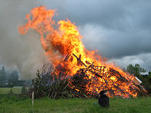 A burning pile of wood in a field.  Furniture and EPAL pallets can be seen in the fire, a brown plume of smoke rises.  A child is sitting in front of the fire.