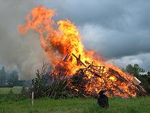 Ein brennender Holzhaufen auf einem Feld. Im Feuer sind Möbelstücke und EPAL-Paletten zu erkennen, eine braune Rauchfahne steigt auf. Vor dem Feuer sitzt ein Kind.