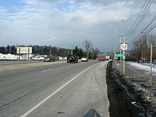 A four-lane highway with a striped median is bordered on both sides by snow-covered areas. A NY 32 shield and reference marker are mounted on a pole to the right of the road.