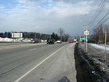 Una carretera de cuatro carriles con una mediana rayada está bordeada a ambos lados por áreas cubiertas de nieve.  Un escudo NY 32 y un marcador de referencia están montados en un poste a la derecha de la carretera.