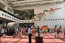 Patrons mill around hall with SpaceShip One, the Spirit of Saint Louis, and the Apollo 11 command module