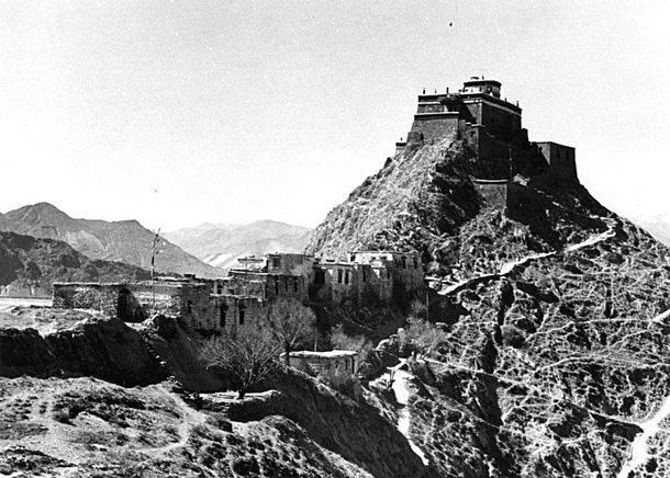 "1938 photo of now destroyed Men Tsee Khang on top of Chagpori (English translation is ""Iron Hill""), taken from the ""Western Gate"" or Pargo Kaling. Both Men Tsee Kang and Pargo Kaling were destroyed during the March 10th, 1959 uprising during which the 14th Dalai Lama exiled to India Now destroyed buildings on the ridge under the Men Tsee Khang in the capitol city of Lhasa, Tibet in 1938, from- Bundesarchiv Bild 135-S-15-46-24, Tibetexpedition, Blick auf Medizinberg (cropped).jpg"