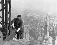 A construction worker on top of the under construction Empire State Building, Chrysler Building behind. 1930.