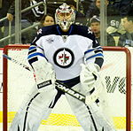 An ice hockey goaltender stands in front of the net. He wears white leg pads and glove and blocker. He is wearing a white jersey with blue shoulders with a jet over a maple leaf inside of a circle for the logo.