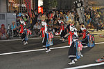 Masked men with swords and traditional dress dancing on a street.