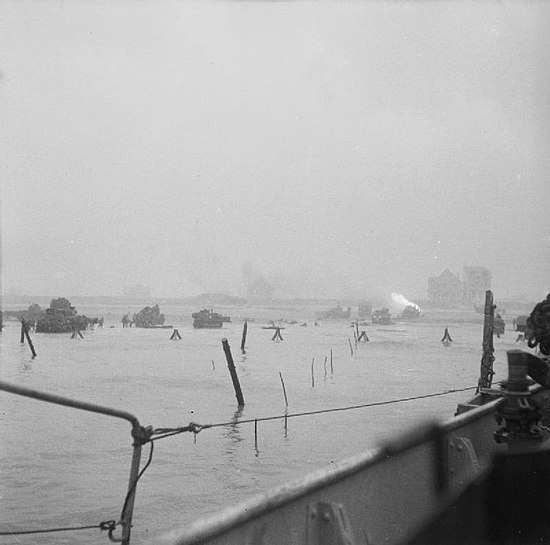Tanks and bulldozers land. A flair burns on shore.