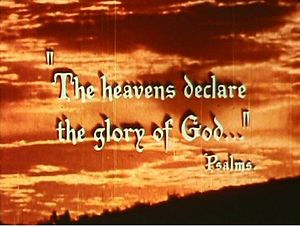 "The quotation ""The Heavens Declare the Glory of God"" and credit ""Psalms"" are overlaid against a photograph of an orange sky and clouds; there is a dark hillside sloping across the bottom right of the photograph. The impression is of a photograph taken at sunrise. The typeface used for the quotation has a Gothic style."