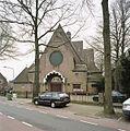 Overzicht van de westgevel met groot rondvenster met glas-in-lood boven de hoofdentree - Hilversum - 20414438 - RCE.jpg