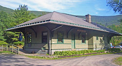 A green building with wooden siding and a peaked black roof viewed at a three-quarters angle. Behind it are railroad tracks and a high wooded ridge.