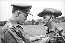 B/W Photo of a gentleman pinning the Military Cross on Harry Smith in military uniform, 1967