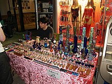 "A man sitting at a table on a sidewalk. On the table are an array of pipes from large and ornate to small and plain. A sign taped to the tablecloth in front says ""Tobacco use only."""