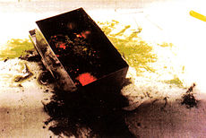 A black block on a table with red spots on top and yellow powder around it.