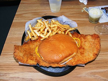 A pork tenderloin sandwich, with a side of french fries