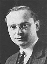 The head and shoulders of a clean-shaven man with hair parted on his left, wearing round, wire-rimmed glasses and a suit and tie