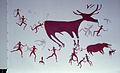 Restored copy of Çatalhöyük mural showing a boar and a deer surrounded by hunters..jpg