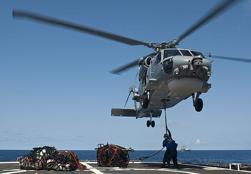 Sailors attach a cargo sling to a Royal Australian Navy S-70B Seahawk helicopter