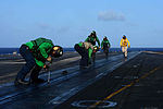 Sailors fasten buttons on the flight deck.jpg