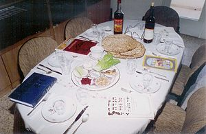 Passover Seder plate - Table set for the seder with a seder plate, salt water, matza, kosher wine and a copy of the Haggadah for each guest
