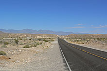 A two-lane asphalt highway passes through a desert landscape dotted with sagebrush and cacti as it heads towards the distant mountains.