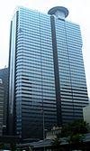 Ground-level view of a blue, glass, rectangular high-rise lined with rows of windows; a small circular pad sits atop the building