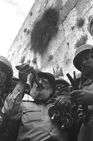 """הרב הראשי של צה""""ל, הרב שלמה גורן, מוקף בחיילי צה""""ל, תוקע בשופר מול הכותל המערבי התמונה צולמה ב-7 ביוני 1967."""