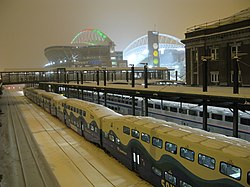 The last commuter train at a train station with a brightly lit stadium nearby. The stadium's roof supports are colored with green and red lights for the Christmas season.