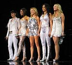 Five woman wearing silver costumes.