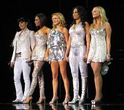 Colour photograph of the Spice Girls standing in a line onstage in 2008.