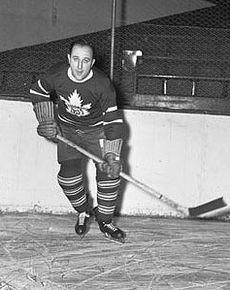 A man in full hockey gear skates toward the camera. He is in a dark jersey with a stylized maple leaf logo and is holding his stick left handed.
