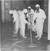 Five members of a clean-up crew scrub the floor while wearing full protective radiation suits.