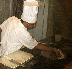 Chef - A chef working with a tandoor, a cylindrical clay oven used in cooking and baking