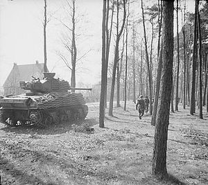 5th Canadian Division - A Sherman Firefly of the 5th Canadian (Armoured) Division assists British troops of the 11th Battalion, Royal Scots Fusiliers, British 49th Infantry Division, to clear the Germans from Ede, the Netherlands, 17 April 1945.