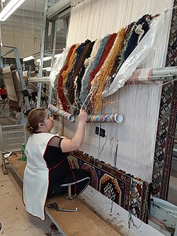 The woman making a carpet and watching TV series.jpg