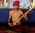 Tibetan detail, Dranyen player in India - lups and his dranyen (cropped).jpg