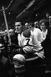 Tim Horton sitting on the bench during a ice hockey game with several other teammates.
