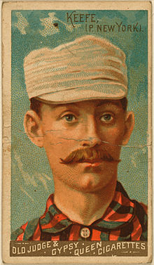 A baseball-card image of a mustachioed man in a red-and-black striped shirt and white pillbox cap