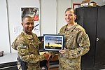 U.S. Air Force Chief Master Sgt. Kenneth Lindsey, left, the command chief master sergeant of the 455th Air Expeditionary Wing, presents a Warrior of the Week award to Staff Sgt. Tyler Schilling, a truck 131009-F-UR349-001.jpg