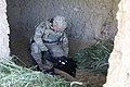 U.S. Army Spc. Micah Roberts uses a portable explosion detector to examine clothes found in a barn during a search for weapons caches, in Parwan province, Afghanistan, May 10, 2011 110510-A-ZM120-109.jpg