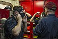 U.S. Navy Damage Controlman 3rd Class Jason DeShields, right, instructs U.S. Naval Academy Midshipman Philip Deturck, left, on how to properly don firefighting equipment aboard the guided missile destroyer USS 140626-N-EI510-032.jpg
