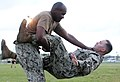 U.S. Navy Electronics Technician 1st Class Duvon Thomas throws Construction Electrician 1st Class Michael Baxter to the ground during a Marine Corps Martial Arts Program (MCMAP) green belt qualification course 130628-N-SD120-001.jpg