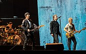 Quatre hommes sur une scène, tous vêtus de vêtements noirs.  Deux jouent de la guitare, un est assis derrière une batterie et un chante dans un pied de micro.