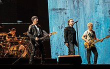 U2 performing on a concert stage. The Edge and Adam Clayton, playing guitars, flank Bono in the foreground, while Larry Mullen, Jr. is behind a drum kit in the background on the left side.
