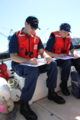 Two Coast Guard auxiliarists review performance qualification workbooks in Portland, Oregon in 2013.