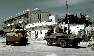 "Unified Task Force - A US Marine 8x8 LAV-25 (Light Armored Vehicle) from 3rd Light Armor Infantry Battalion (left), and Italian Soldiers in a 4x4 Fiat-OTO Melara Type 6614 Armored Personnel Carrier (right), guard an intersection on the ""Green Line"" in Mogadishu."