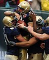 US Navy 041230-N-9693M-005 U.S. Naval Academy Midshipman 1st Class Aaron Polanco celebrates his touchdown with members of the offensive line in the 1st quarter of play against the Lobos of New Mexico at the Emerald Bowl in San.jpg