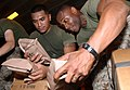US Navy 050101-M-5538E-056 Lance Cpl. Konrad U. Nikolao, left, and Sgt. Shannon R. Haynes, of the 15th Marine Expeditionary Unit (MEU) helps prepare pallets of Meals Ready to Eat (MREs).jpg